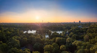 An idyllic park in the Englischer Garten of Munich with a beautiful lake in an aerial view.