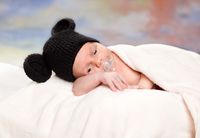 newborn baby in mouse costume sleeping on a fur bed