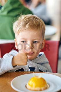 Boy eating dessert in cafe
