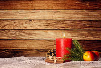 Candle with christmas decoration in front of wooden wall