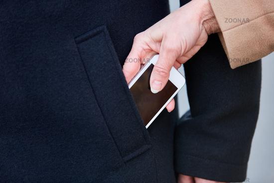 Hand einer Frau beim Stehlen von Smartphone