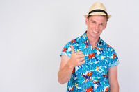 Happy young handsome tourist man with blond hair giving thumbs up