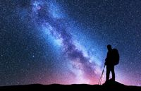 Man with backpack and trekking poles against Milky Way