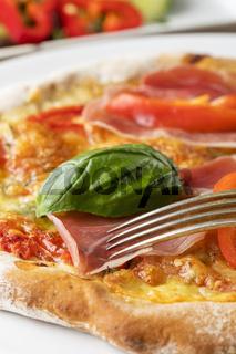 Detail einer Pizza mit Schinken und Basilikum