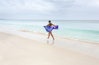 Female in motion with Australian flag running along the beach