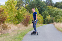 Young caucasian man rides electric mountainboard on road