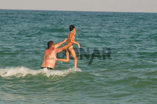 Father casts his daughter high in the waters of the sea. Family jumping game in the ocean.
