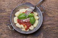 Nahaufnahme von Gnocchi mit Sauce auf Holz