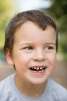 Outdoors closeup portrait of laughing freckled boy with dark hair and brown eyes