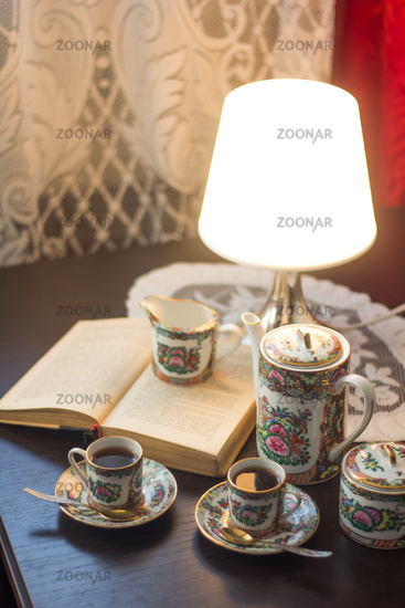 Cups with coffee on a table with a lamp and a book. Cups of coffee. Hot drink. Spiritual gatherings. Koffe break