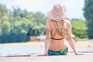 Junge Frau sitzt in der Sonne auf einem Steg