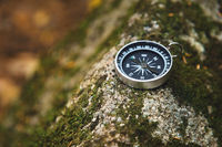 Magnetic compass with a black dial on a wild stone covered with green moss. The concept of finding the way and navigation