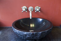 black stone sink at the red wall