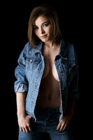 Pretty sexy girl in unbuttoned jeans jacket shot