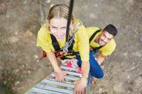 Junge Frau im Kletterpark angeseilt auf der Leiter