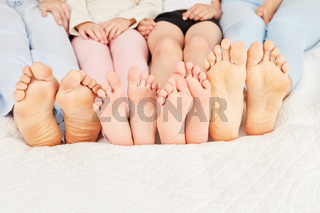 Viele nackte Füße einer Familie im Bett