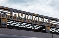 Hummer car logo and slogan against the sky