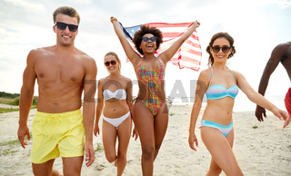 happy friends with american flag on summer beach