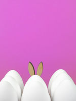 Easter background with white Easter eggs and Easter bunny isolated on pink