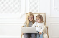 Two adorable litle sisters using their computer laptop together