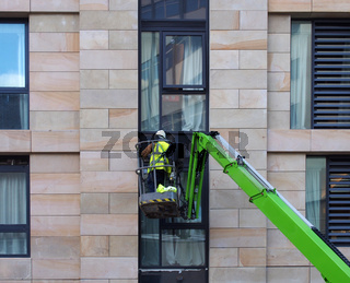an unidentifiable construction worker in a green aerial work platform on a large housing urban construction site