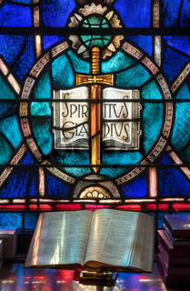 Light from stained glass window falls on open bible in american church