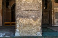 Ornate engraved stone wall with ruined floral patterns at Ibn Tulun Mosque, Cairo, Egypt