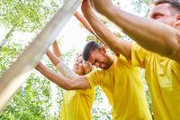 Junges Team stemmt sich gegen ein Holzbrett