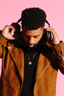 Stylish, handsome and cool African American man with beard, listening to music, isolated on pink studio background