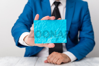 Man holds empty blue paper with copy space in front of him. Business concept with man in a suite and a tie. Blue space for advertising message.