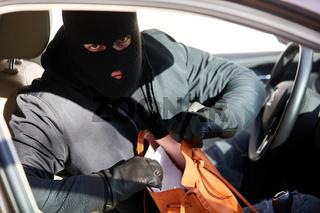 Dieb im aufgebrochenen Auto beim Handtasche stehlen