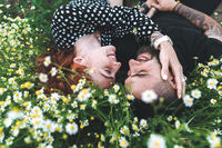 Young couple lies on the field with daisies.