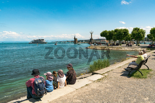 tourists enjoy a beautiful summer day on the shores of Lake Constance with ships passing by