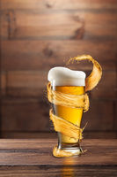 A glass of fresh beer with foam and a splash on a dark wooden background with copy space.