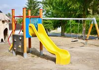 Yellow slide and chain swings in the empty playground.