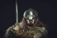 Viking, Scandinavian warrior with helmet and war paintings, wears a sword and a cape of animal skin