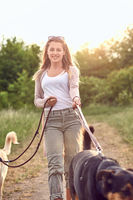 Smiling pretty blond woman walking her two dogs
