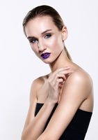 Beauty portrait of young woman with violet lips makeup
