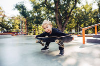 Little boy trying to pick up a skateboard