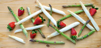 moderne Komposition von grünem und weißem Spargel mit Erdbeeren auf Holz