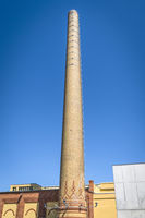 Tall chimney made of bricks on a factory