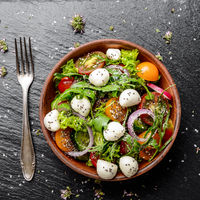 Flat lay of vegetable salad with mozzarella cheese, lettuce, cherry tomatoes, radish, cucumber, onion and basil in clay dish