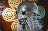 Viking helmet with chain mail of iron on red shield of wood and golden triskel