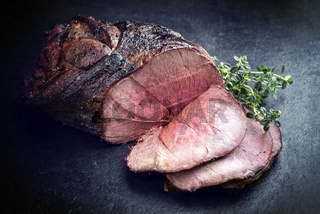 Barbecue dry aged haunch of venison with herbs as close-up on a board