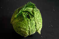 Closeup of savoy cole cabbage on black desk with marble effect.