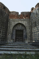Stone masonry wall and main gate with heavy-duty door at Sardar Purandare Wada, Saswad, Pune