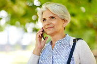 senior woman calling on smartphone in summer park