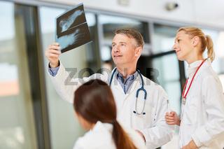 Oberarzt und Team besprechen Röntgenbild