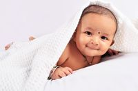 Cute baby sleeping on bed on stomach laughing, Pune, Maharashtra.