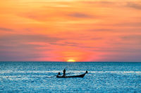 Fishing boat in sea at sunset